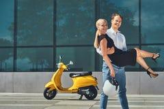 Glückliche attraktive Paare in der Liebe - hübscher stilvoller Kerl hält auf Händen seine reizend blonde Freundin nahe einem Gelb Lizenzfreie Stockfotos