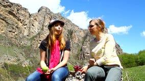 Glückliche auf einem Felsen sitzende und essende Familienmutter und -tochter trägt draußen Früchte stock footage