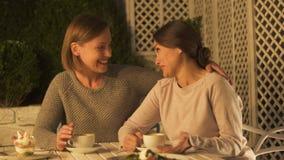 Glückliche auf Terrasse, trinkendem Kaffee sitzende, plaudernde und umarmende Schwestern, Vertrauen stock video