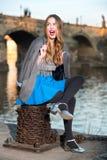Glückliche aufgeregte Frau, die nahe Fluss in der Stadt sitzt Stockfoto