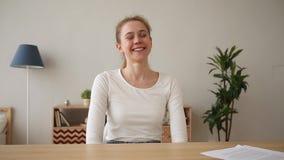 Glückliche aufgeregte Frau, die am Schreibtisch plaudert sitzt, Webcam betrachtend stock footage