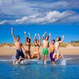 Glückliche aufgeregte jugendlich Jungen und Mädchen setzen das Springen auf den Strand Lizenzfreies Stockfoto