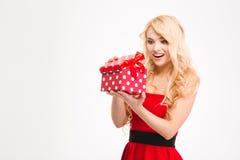 Glückliche aufgeregte junge blonde Frau im roten Kleid öffnete Geschenk Stockbilder