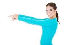 Glückliche, aufgeregte junge Frau, die auf Kopienraum zeigt Lizenzfreies Stockfoto