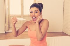 Glückliche, aufgeregte junge Frau, die einen Schwangerschaftstest betrachtet das positive Ergebnis in der Freude hält stockbild