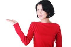 Glückliche, aufgeregte junge Frau, die Kopienraum auf ihrer Palme darstellt lizenzfreie stockfotos