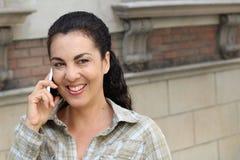 Glückliche aufgeregte lachende Frau von mittlerem Alter, die draußen auf städtischem Hintergrund der Stadt des Handys spricht Lizenzfreie Stockfotos