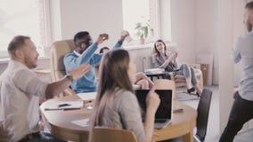 Glückliche aufgeregte multiethnische Büroangestellte feiern Erfolg zusammen mit Teamleiter in der modernen coworking Zeitlupe stock video