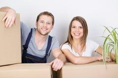 Glückliche aufgeregte Paare, die auf ein neues Haus sich bewegen Lizenzfreie Stockfotos