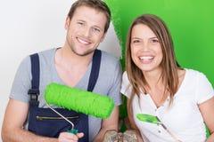 Glückliche aufgeregte Paare, die ihr neues Haus malen Stockfoto