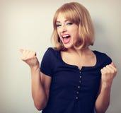 Glückliche aufgeregte Siegerfrau mit geöffnetem Mund Glückliche blonde Junge Lizenzfreie Stockfotos