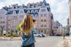 Glückliche, aufgeregte, stilvolle junge Frau, die Foto des Marksteins in der neuen alten schönen euripean Stadtrückseite hinter A lizenzfreie stockfotografie