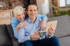 Glückliche aufwerfender Mutter und Sohn beim Betrachten des gestalteten Fotos stockfotografie