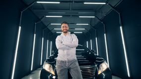 Glückliche Autosorgfaltarbeitskraft steht vor einem Automobil stock video footage