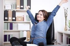 Glückliche Büro-Frau auf dem Stuhl, der ihre Arme verlängert Lizenzfreie Stockfotografie