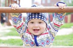 Glückliche Babyholding des Bergsteigers auf Spielplatz Lizenzfreie Stockbilder