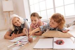 Glückliche begeisterte Kinder, die zusammen malen Lizenzfreies Stockfoto