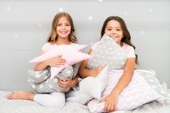 Glückliche beste Freunde oder Geschwister der Mädchen in den netten stilvollen Pyjamas mit Kissen Sleepoverpartei Schwestern spie stockfoto