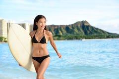 Glückliche Bikinifrau, die auf Waikiki-Strand Hawaii surft Stockfotos