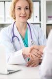 Glückliche blonde Ärztin, die Hände mit Patienten beim Sprechen mit ihr rüttelt Medizin-, Gesundheitswesen- und Hilfskonzept Stockbilder