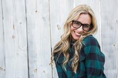 Glückliche blonde Aufstellung mit den Gläsern, die Kamera betrachten Lizenzfreie Stockbilder