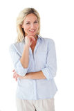 Glückliche blonde Aufstellung mit der Hand auf Kinn Stockfoto