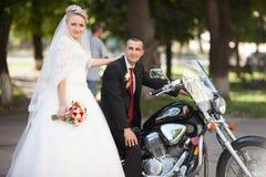 Glückliche blonde Braut, die nahe bei ihrem geliebten steht, das auf a sitzt Stockbilder