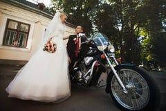 Glückliche blonde Braut, die nahe bei ihrem geliebten steht, das auf a sitzt Lizenzfreies Stockfoto