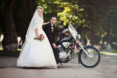 Glückliche blonde Braut, die nahe bei ihrem geliebten steht, das auf a sitzt Stockfotografie