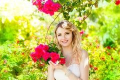 Glückliche blonde Braut, die Spaß auf einem tropischen Garten hat Hochzeit und h Stockbilder