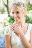 Glückliche blonde Braut mit der Hand auf Kasten Stockfoto