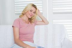 Glückliche blonde Entspannung auf der Couch Lizenzfreies Stockbild