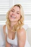 Glückliche blonde Entspannung auf der Couch, die an der Kamera lächelt Stockfoto