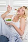 Glückliche blonde Entspannung auf der Couch, die einen Salat isst Lizenzfreie Stockfotografie