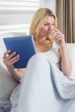 Glückliche blonde Entspannung auf der Couch mit Glas Weißwein- und Tabletten-PC Lizenzfreies Stockbild