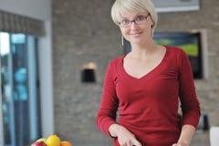 Glückliche blonde Frau bereiten Nahrung in der Küche zu Stockbild