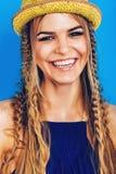 Glückliche blonde Frau in der blauen Spitze und im gelben Hut Lizenzfreies Stockfoto