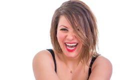 Glückliche blonde Frau, die über die Kamera lacht Stockfotos