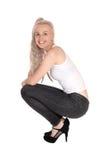 Glückliche blonde Frau, die auf Boden sich duckt Lizenzfreie Stockfotografie