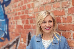 Glückliche blonde Frau, die an der Backsteinmauer sich lehnt Stockbild