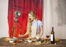Glückliche blonde Frau, die an der Küche kocht Lizenzfreie Stockfotos