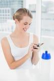Glückliche blonde Frau, die eine Textnachricht sendet Stockfoto