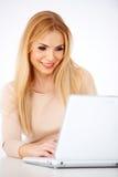 Glückliche blonde Frau, die an einem Laptop arbeitet Lizenzfreie Stockbilder