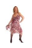 Glückliche blonde Frau, die in einem Sommerkleid steht Stockfoto