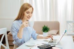 Glückliche blonde Frau, die an ihrem Laptop und trinkenden Tee arbeitet Lizenzfreies Stockfoto