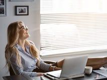 Glückliche blonde Frau, die sich nach der Arbeit im Büro entspannt Lizenzfreie Stockfotografie