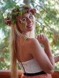 Glückliche blonde Frau, die um sich dreht und mit Herbstlaub auf Kopf lächelt Stockbilder