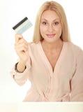 Glückliche blonde Frau, die unbelegte Kreditkarte zeigt Stockfoto