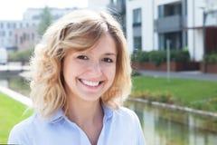 Glückliche blonde Frau in einem Wohngebiet Stockbild