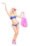 Glückliche blonde Frau im Badeanzug, der einen Strandbeutel anhält Lizenzfreies Stockfoto